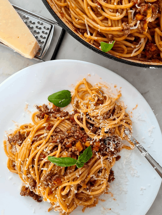 A plate of spaghetti bolognese with parmesan cheese sprinkled on top
