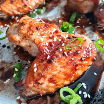 Close up image of sticky soy chicken wing sprinkled with sesame seeds and finely sliced scallions.
