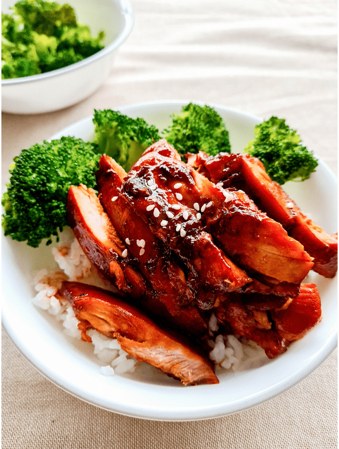 Close up of a bowl of rice topped with broccoli and sliced teriyaki chicken sprinkled with sesame seeds