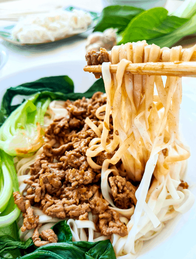 Close up of noodles being picked up by a pair of chopsticks
