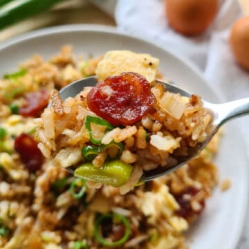 Close up of a spoonful of Chinese sausage fried rice with a full plate in the background