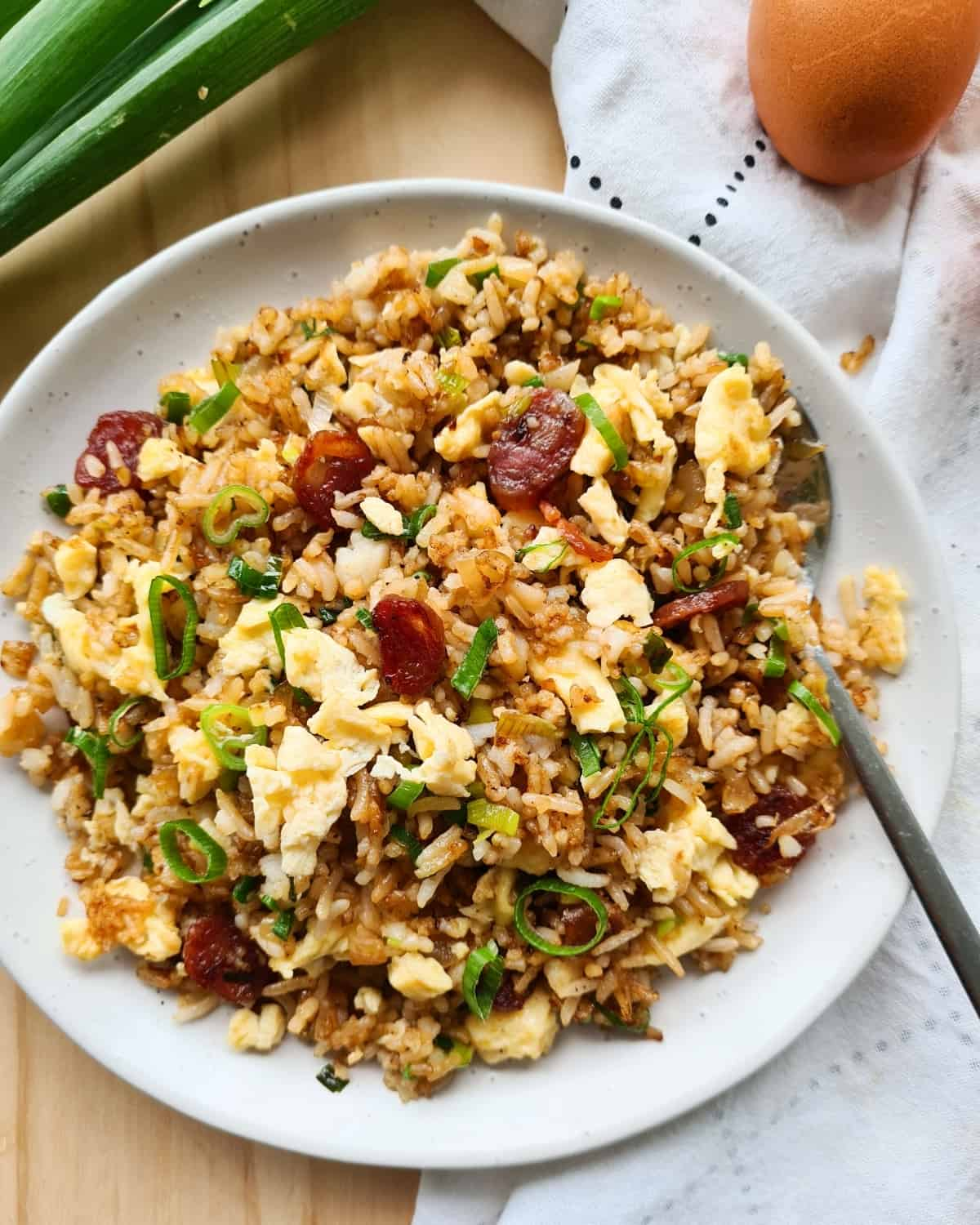 Overhead shot of a plate of Chinese sausage fried rice with a spoon on the plate.
