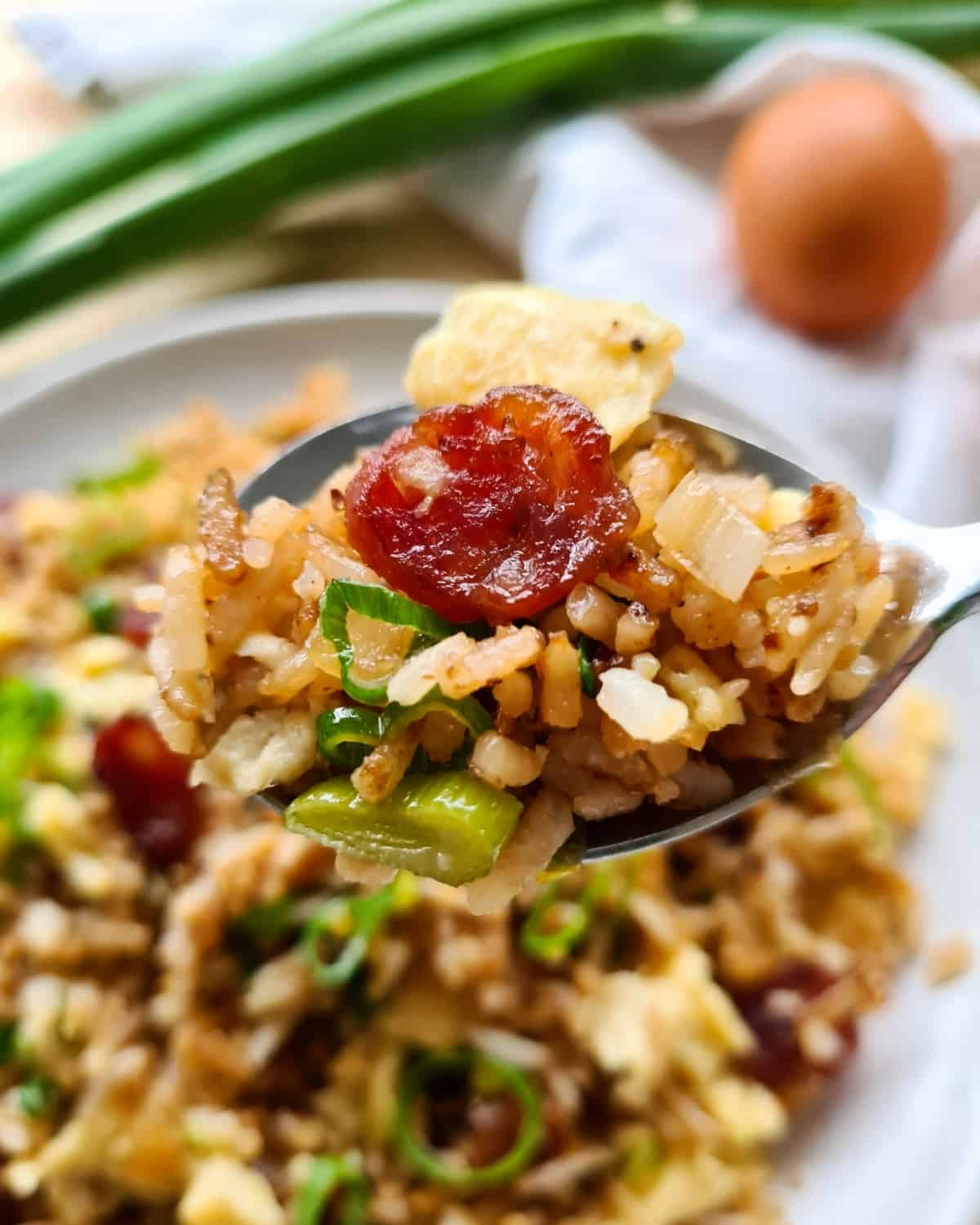 Close up image of a spoonful of Chinese sausage fried rice. A full plate in the background