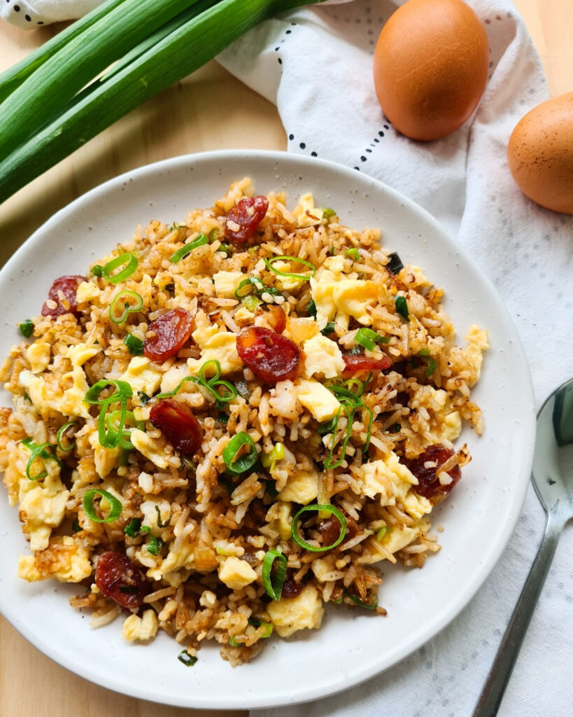 A full plate of Chinese sausage fried rice with a spoon on the right hand side. Whole eggs and raw spring onions in the background
