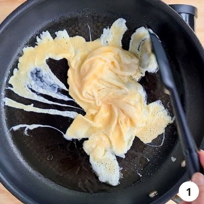 Eggs scrambling in a hot pan