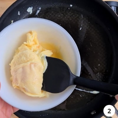 Scrambled eggs removed from hot pan, into a white bowl