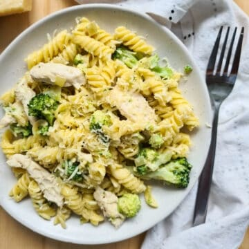 A plate of chicken and broccoli pasta with grated parmesan cheese on top.