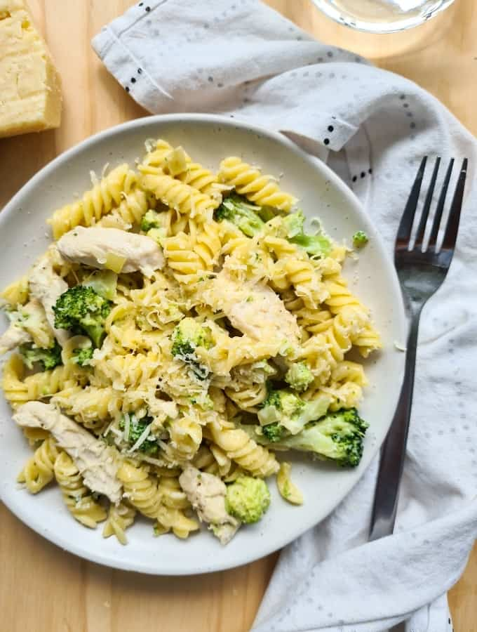 A plate of cooked chicken and broccoli pasta with freshly grated parmesan cheese on top. A fork on the right, on top of a loosely folded kitchen towel.