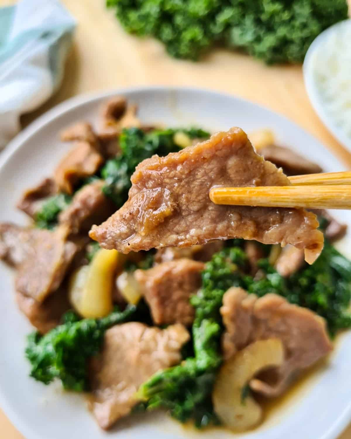 close up image of a piece of cooked, velvety beef slice held up by chopsticks
