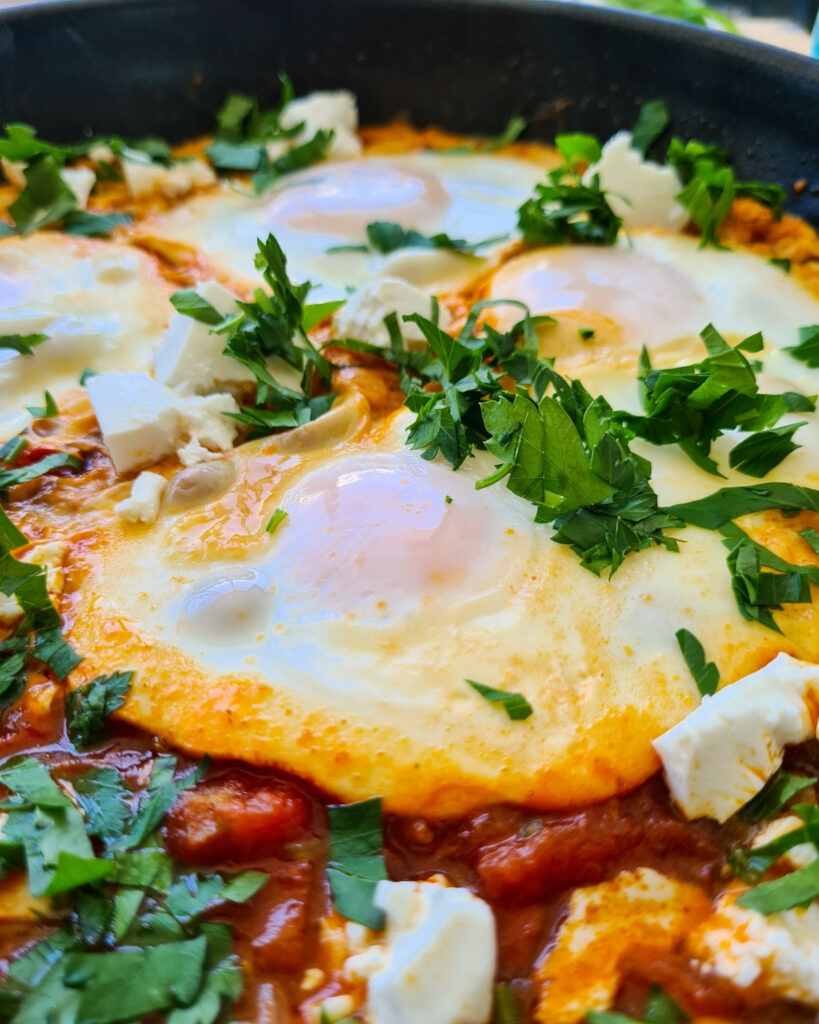 Close up of shakshuka with feta in a pan