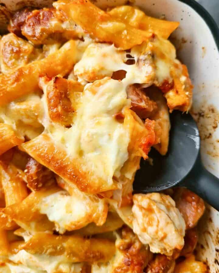 Close up of freshly baked chicken and chorizo pasta bake being scooped by a spatula