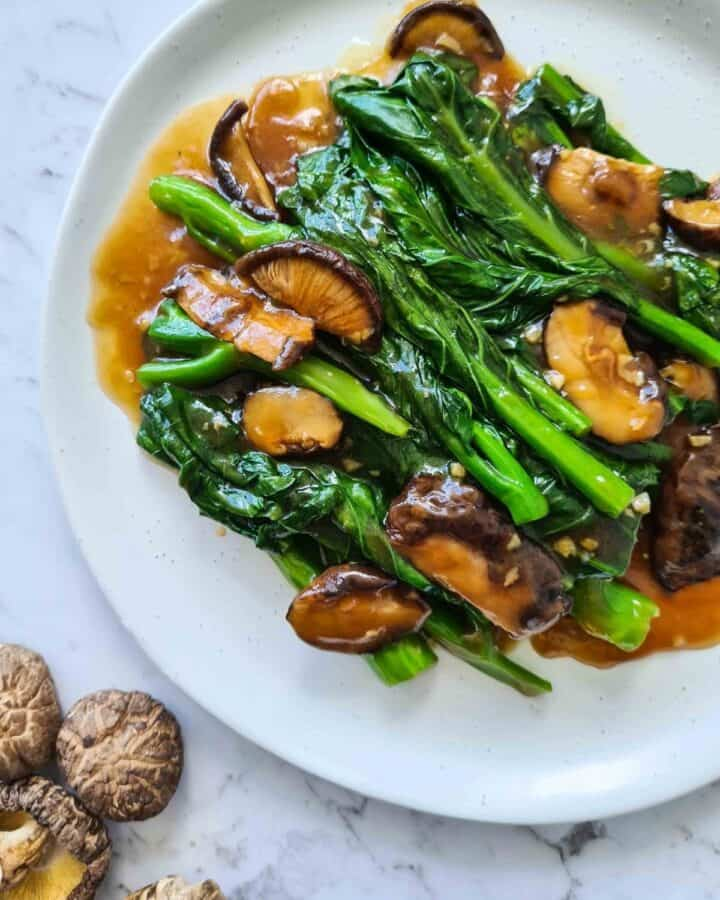 Close up of Chinese broccoli with shiitake mushrooms on top left corner