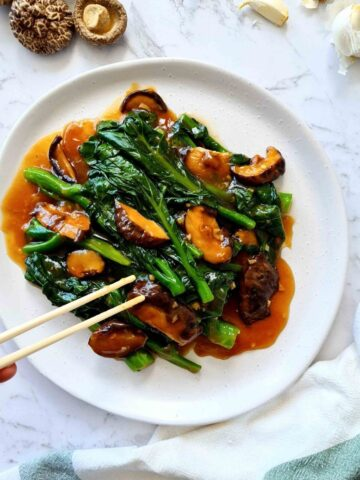 Plate of Chinese broccoli with mushrooms and sauce