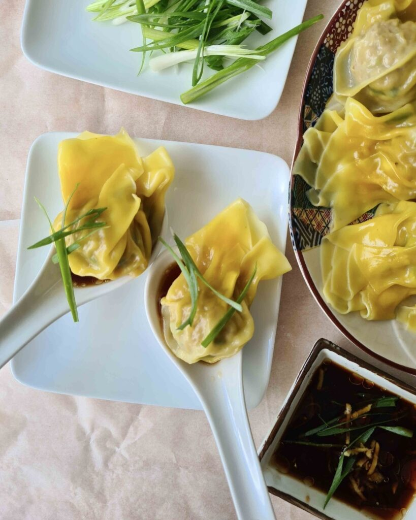 2 pork wontons on Chinese soup spoons with dipping sauce