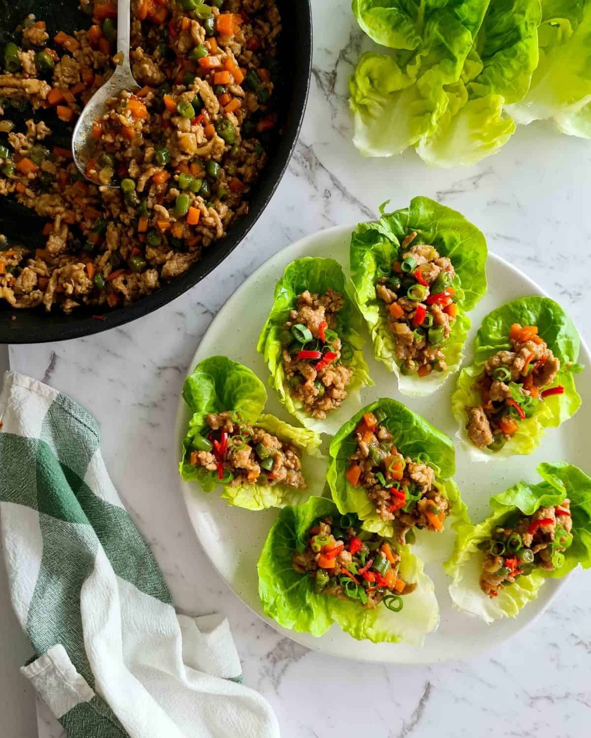 Overhead view of a plate full of lettuce wraps with extra filling and lettuce on the side