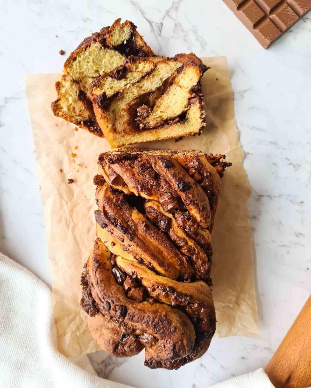 A loaf of chocolate brioche babka half sliced