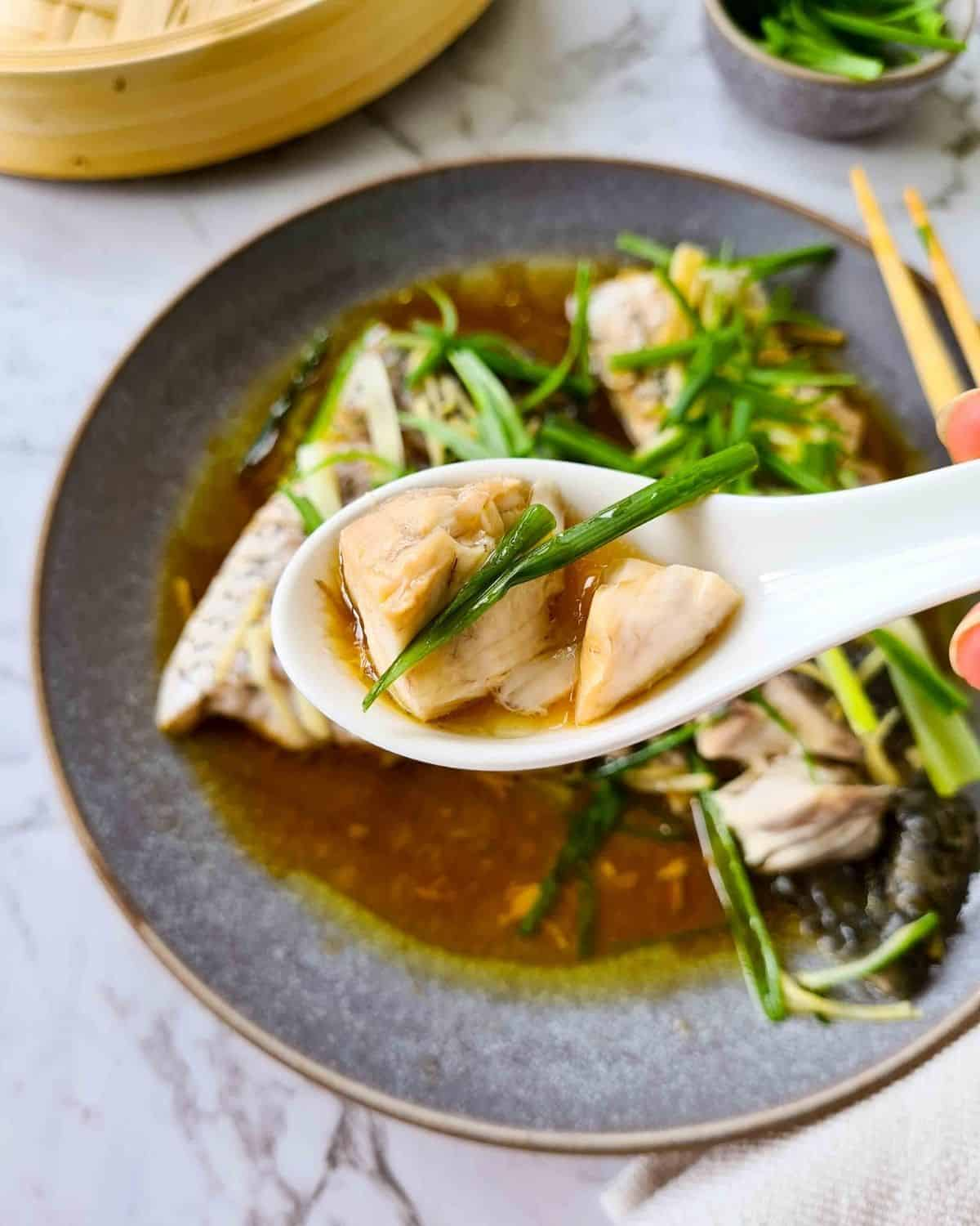 A close up spoonful of steamed fish with delicious ginger and spring onion sauce