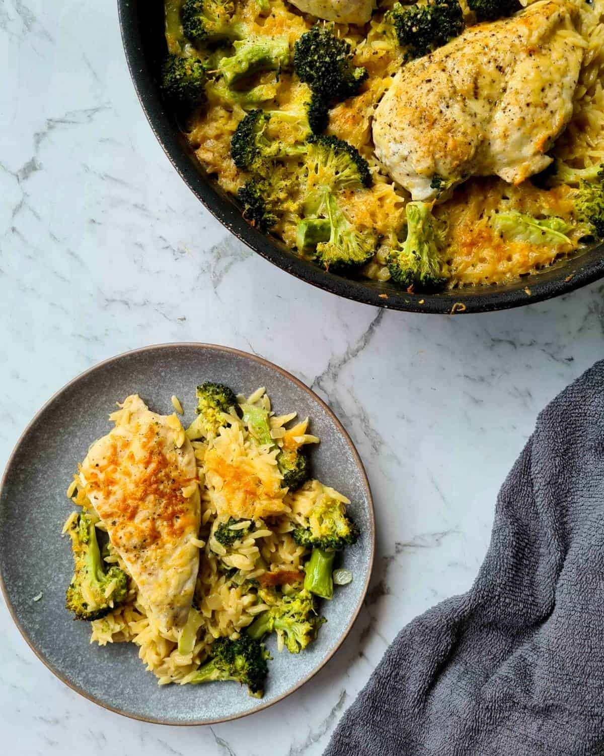 A plate serving of baked chicken and broccoli risoni with the full pan on the top right hand corner
