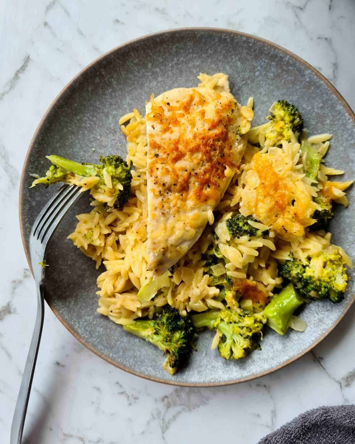 Close up of a plate of baked chicken and broccoli risoni
