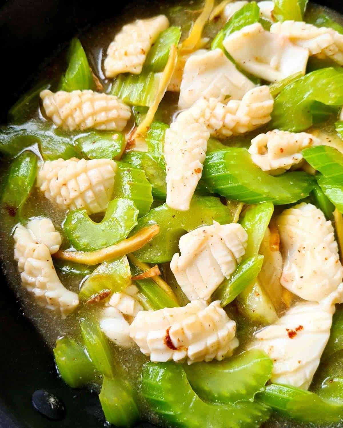 Close up of cooked squid, celery and ginger with plenty of sauce.