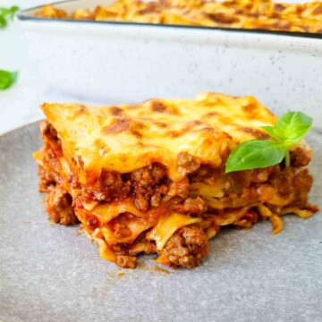 Sideview of a slice of lasagna showing all 4 layers. A tray of lasagna in the background, blurred
