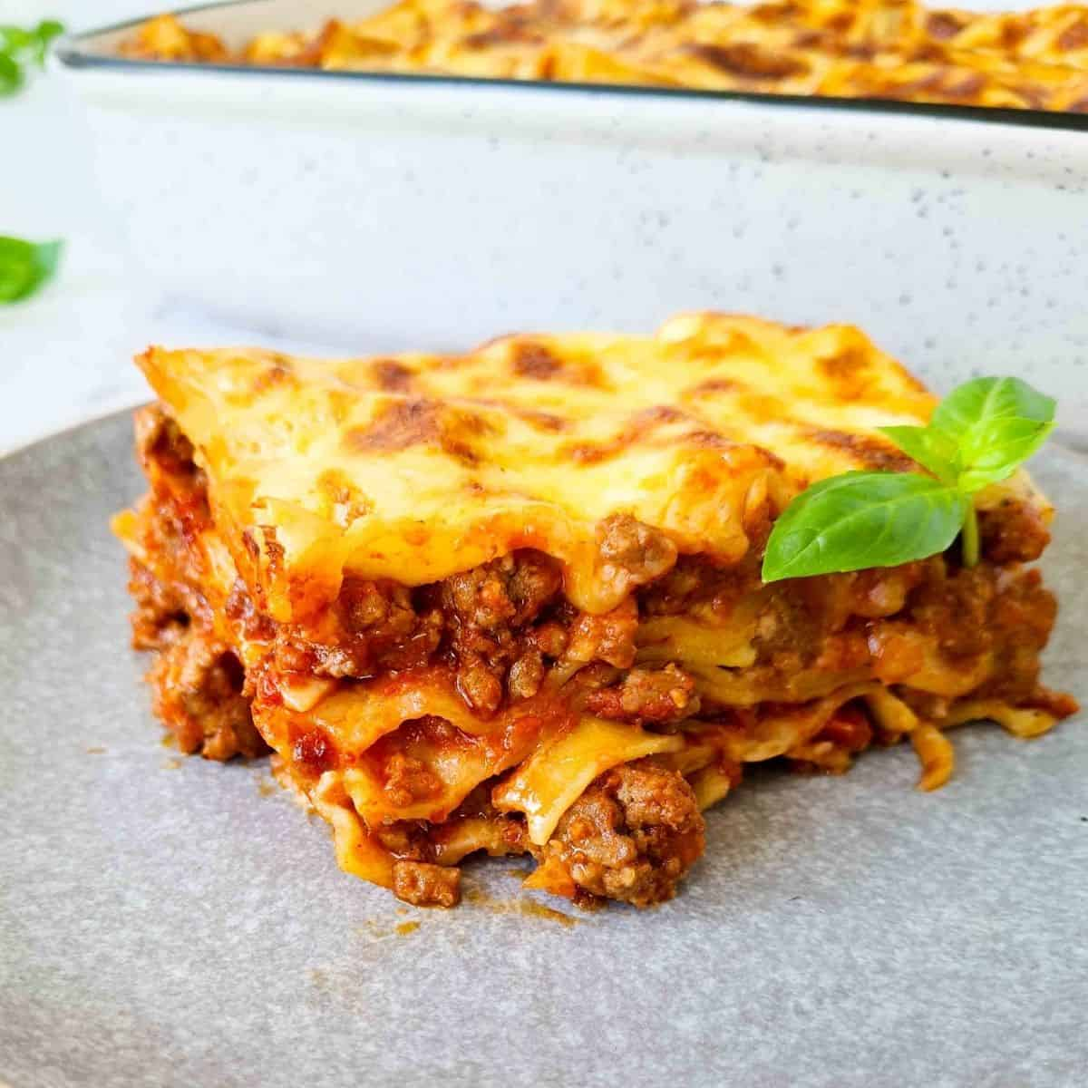 Side view of a slice of lasagna, showing all 4 layers with lots of chunky meaty bolognese in each layer.