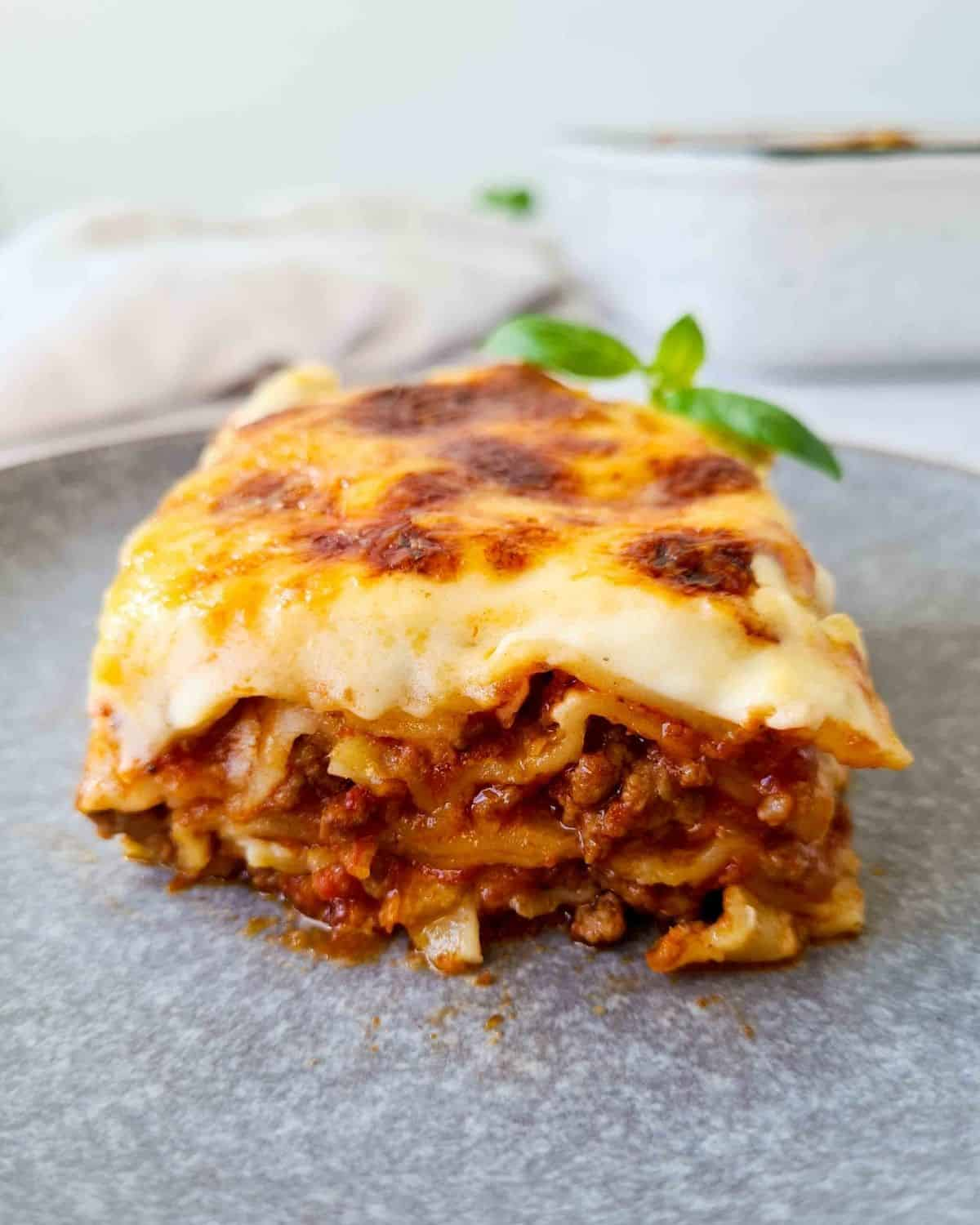 Side front on view of a slice of lasagna on a grey plate with emphasis of a thick layer of bechamel sauce.