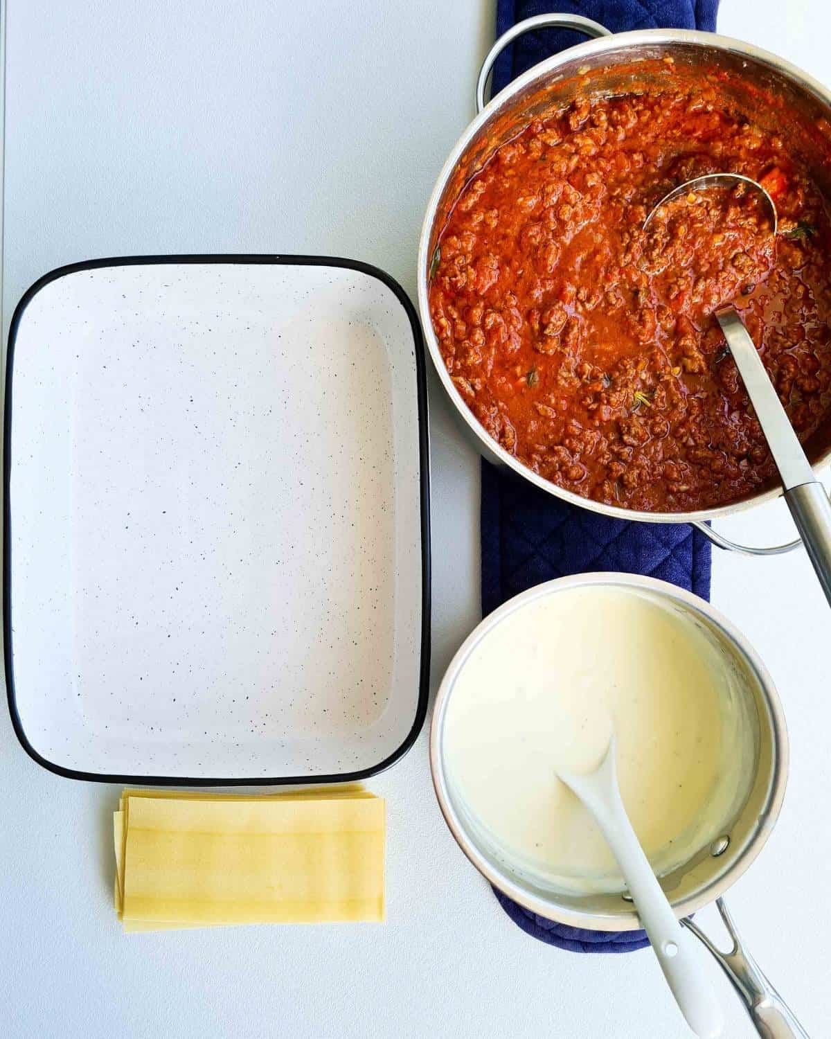 A laid out work station with a pot of cooked beef bolognese, a pot of bechamel sauce, a oven dish and a stack of dried lasagne sheets