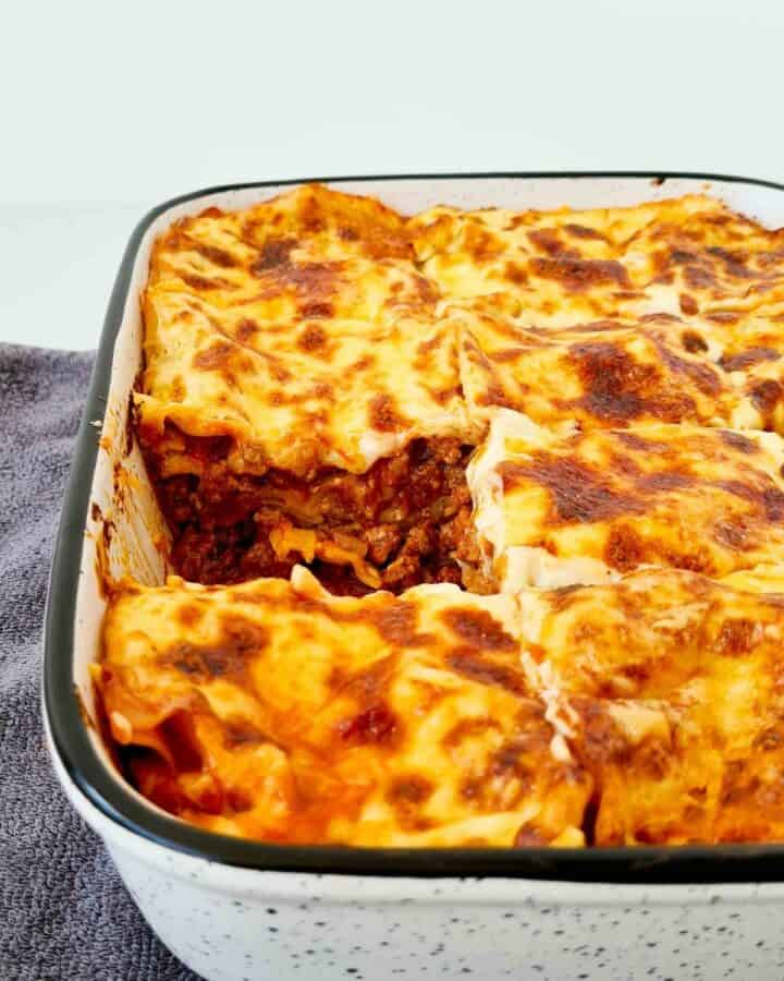 A side view of a tray of lasagna, cut and divided into squares with a piece taken out.