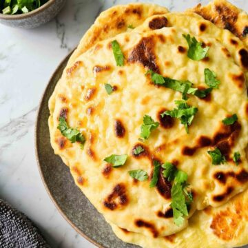 Close up plate full of yoghurt naan bread brushed with butter and fresh coriander