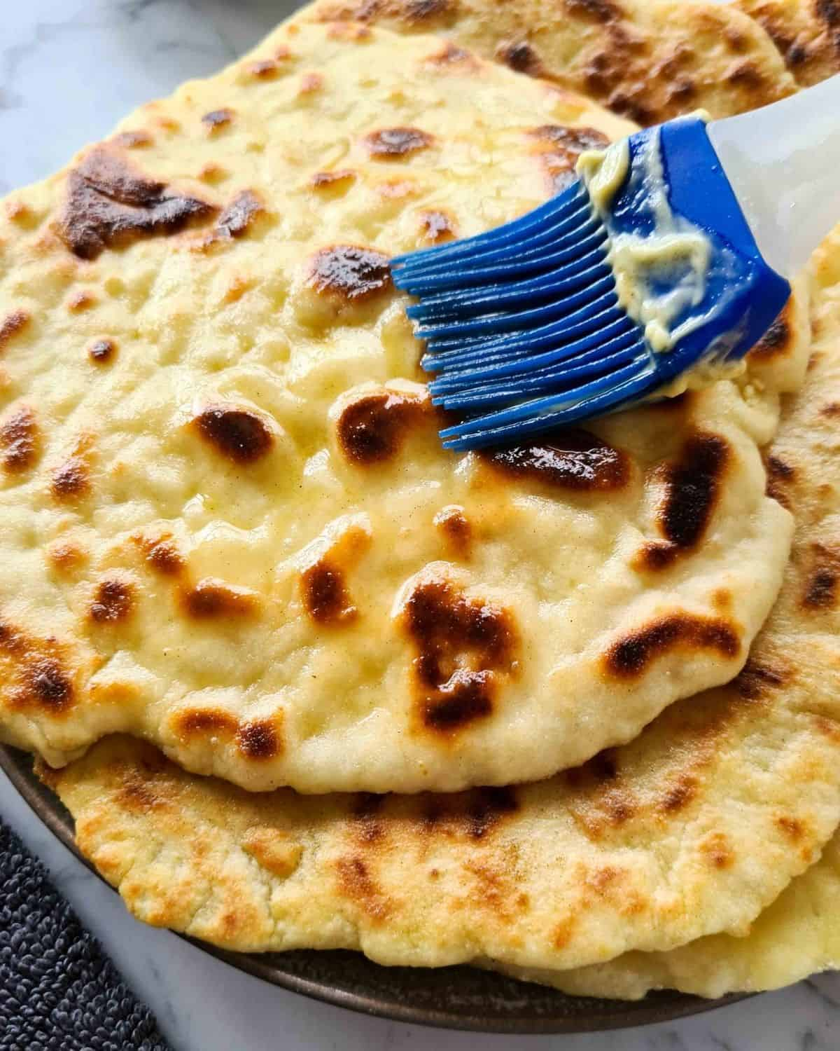 Close up of butter being brushed onto a piece of freshly cooked naan bread with a blue brush.