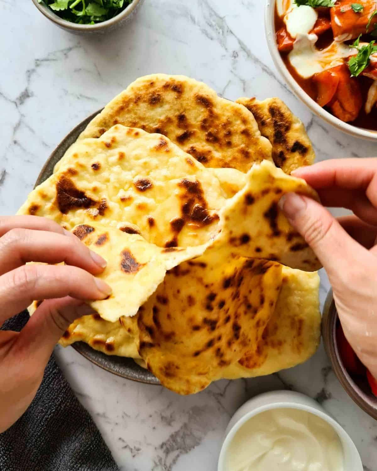A piece of naan bread being teared apart