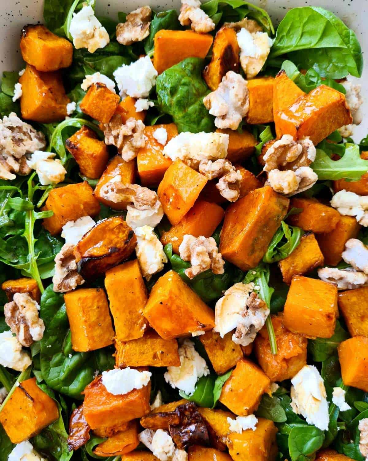 Close up of a large serving dish of pumpkin salad with lots of walnuts and pumpkin