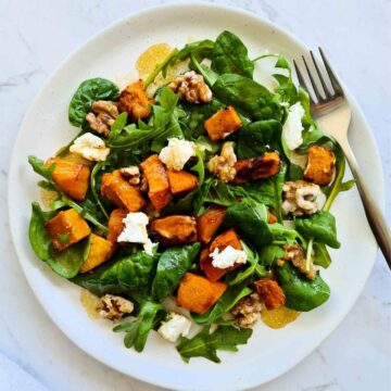 Fresh pumpkin salad on a white plate with a fork