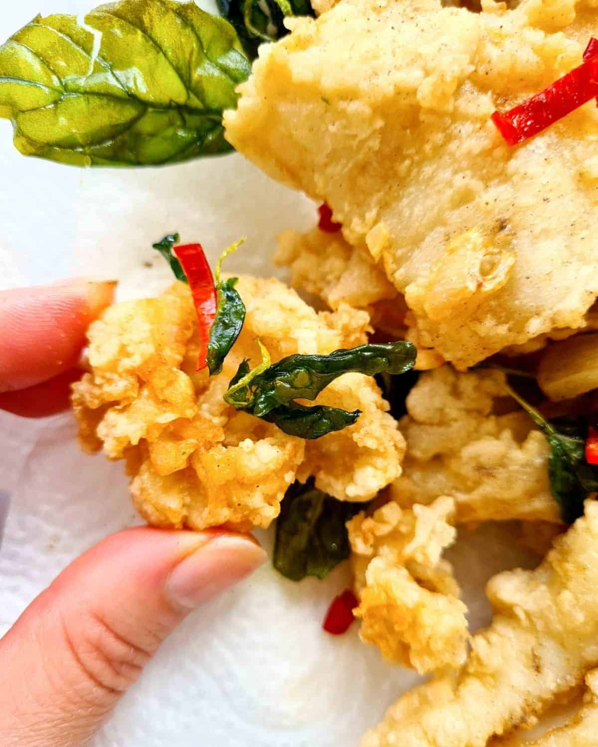 Close up image of a piece of fried crispy squid held up by two fingers