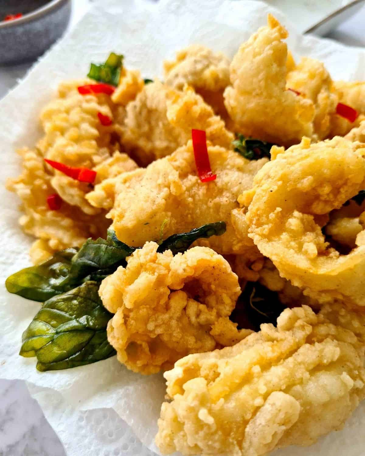 Close up, side view of crispy coated squid decorated with bail crisps and chilli