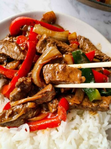 a plate of beef with black bean stir fry with rice