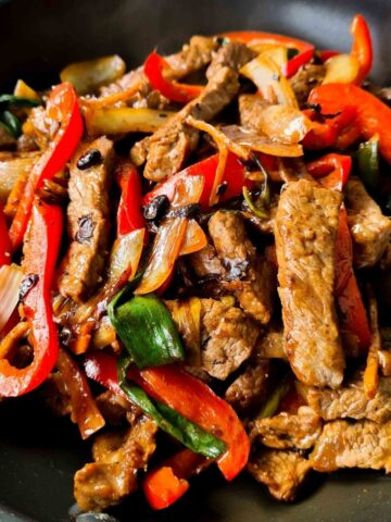Close up of beef stir fry in a black frying pan