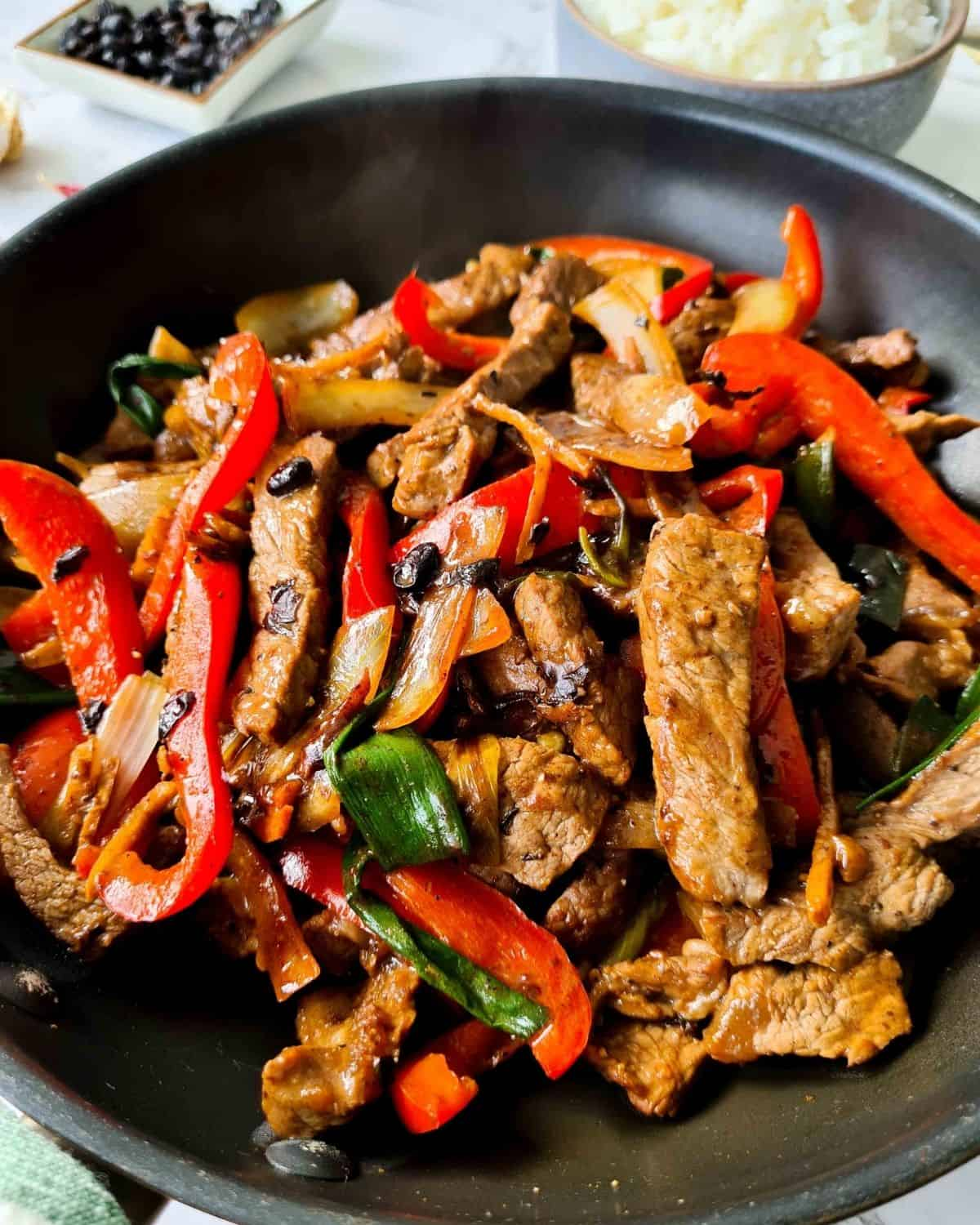 Close up of freshly cooked beef stir fry with black bean sauce in a black pan