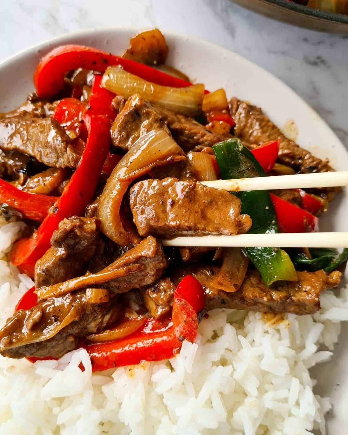 Extrem close up of cooked beef and vegetables coverd in glossy sauce with a side of rice on a plate.