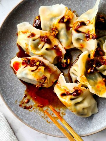 Close up of a plate of boiled dumplings drizzled in chilli oil dipping sauce