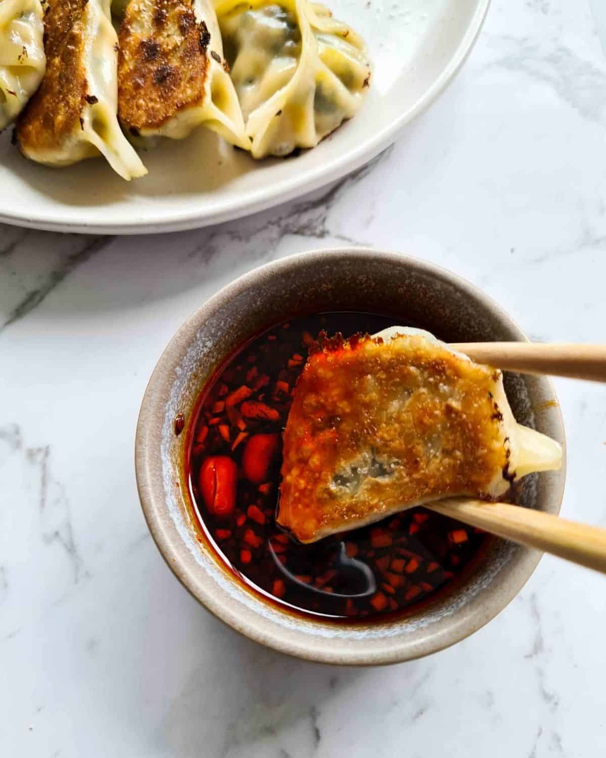 Close up of a potsticker being dipped into a chili oil sauce, held up by a pair of chopsticks