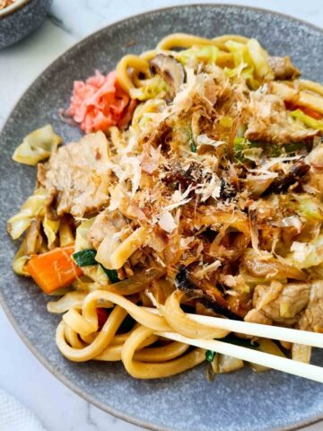 Side view of a plate of udon stir fry with chopsticks