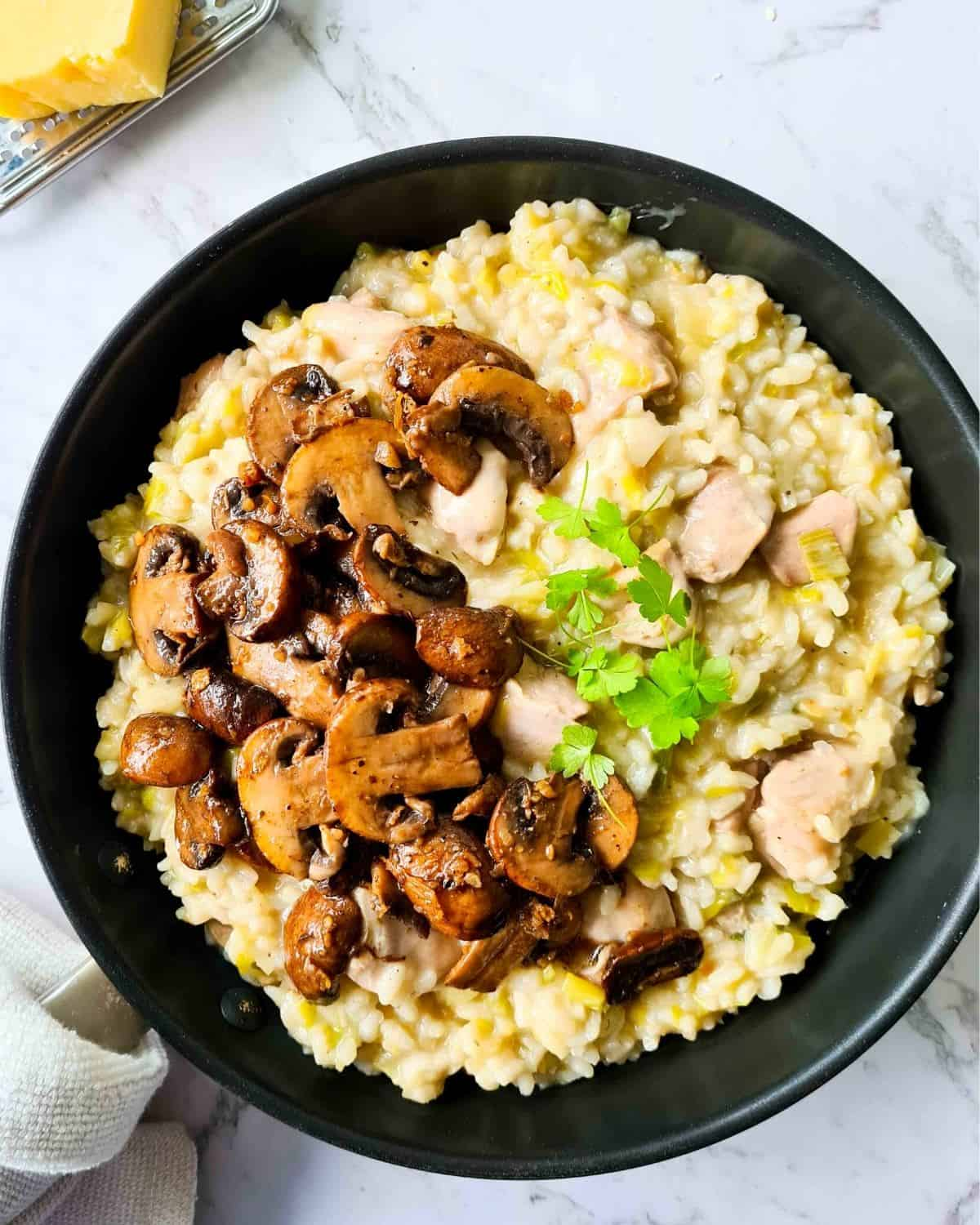 Cooked risotto in a large black pan