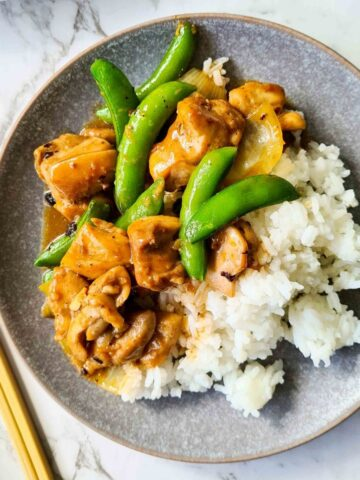 chicken black bean stir fry served with rice on a grey plate