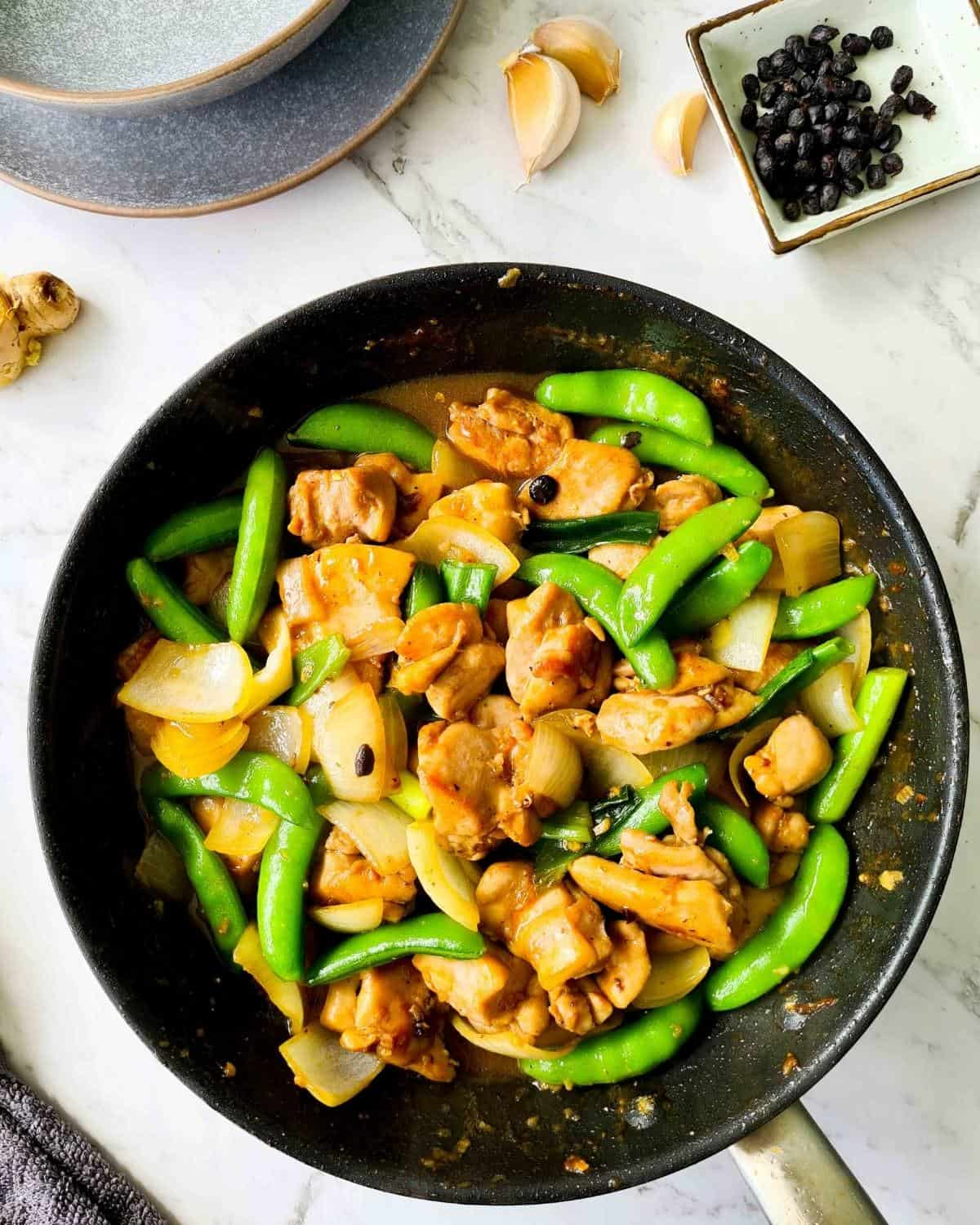 Chicken black bean sauce with sugar snap peas in a small pan