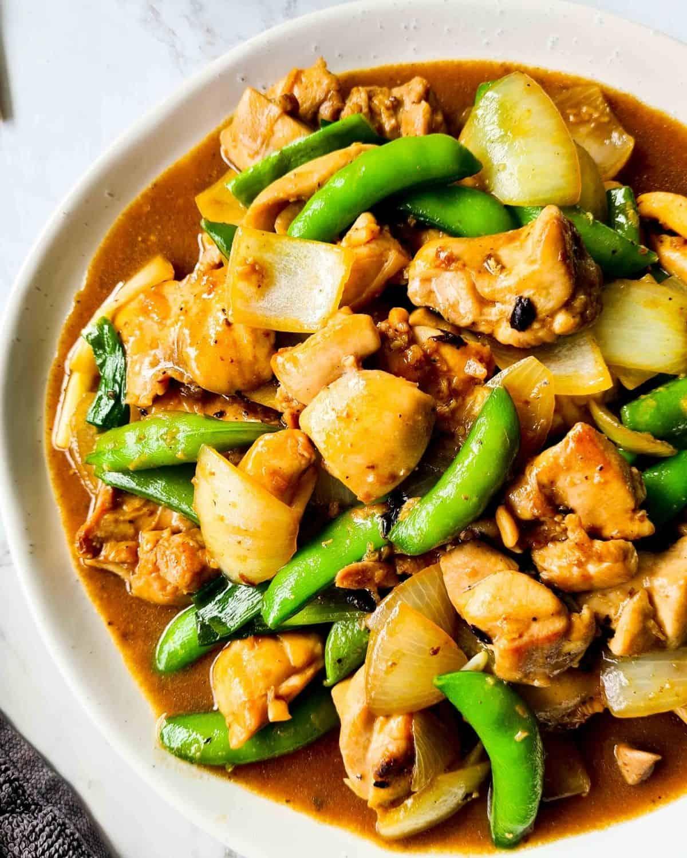 Chicken, sugar snap peas in black bean sauce on a white plate