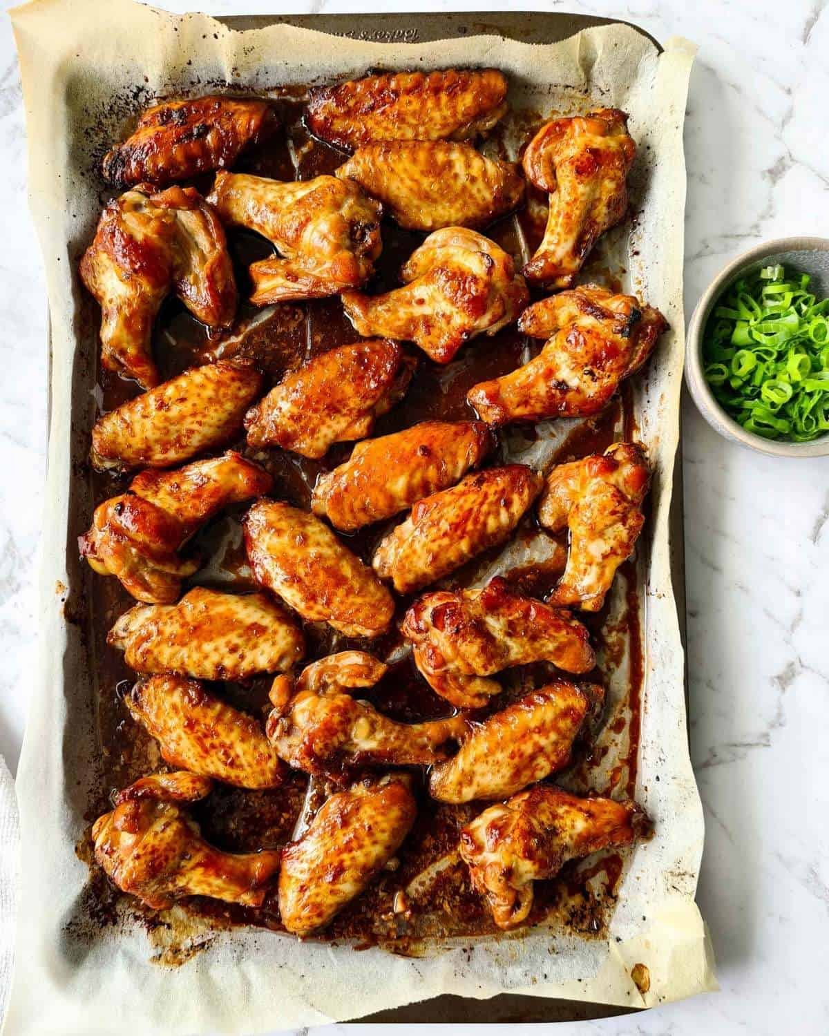 Freshly baked soy chicken wings on a lined baking tray