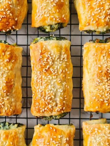 Golden spinach and ricotta rolls on a cooling rack