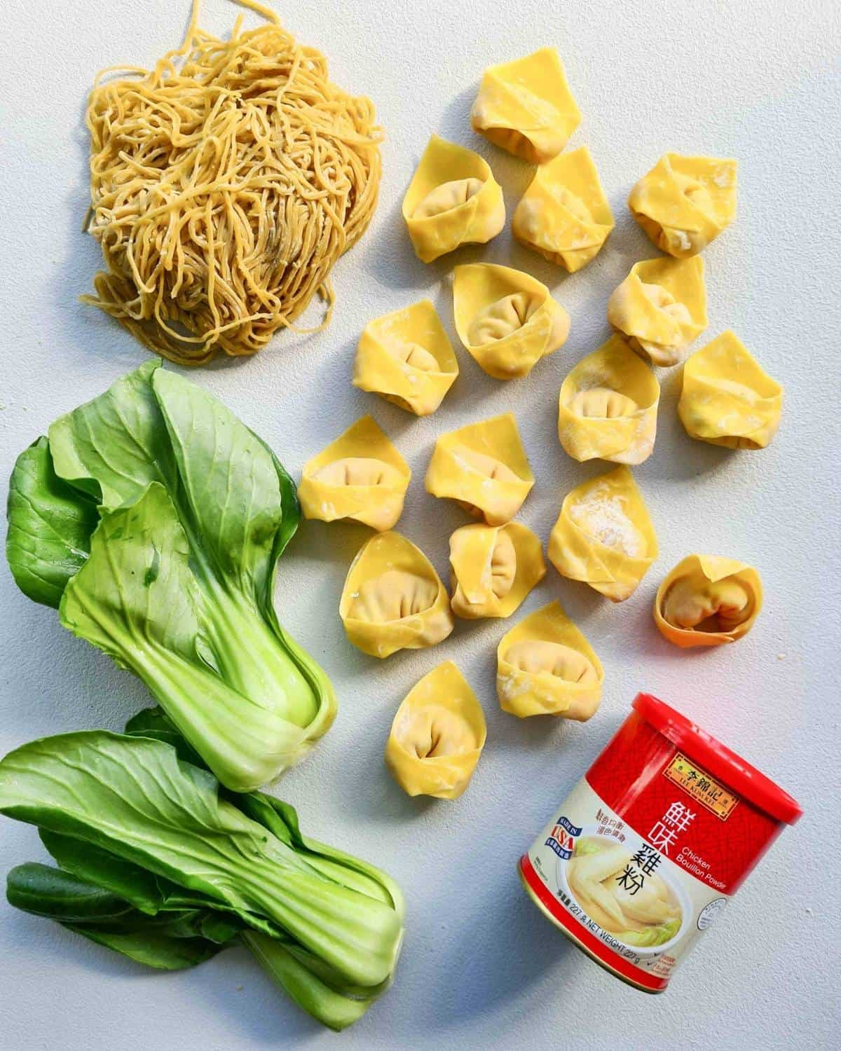 Folded wontons, egg noodles and bok choy ready for cooking